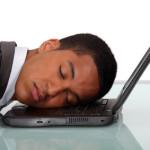 Young businessman asleep on laptop